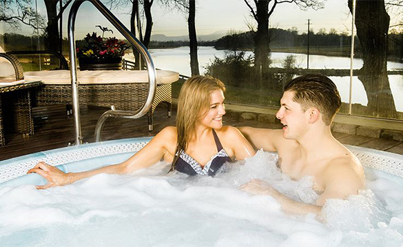 Couple in a jacuzzi hot tub at the Killyhevlin Hotel/