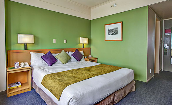 double bedded hotel room with green painted walls and blue carpet/