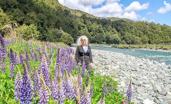 lady standing on a rocky shoreline next to some purple foxgloves with a forest behind and a river to the right of her/