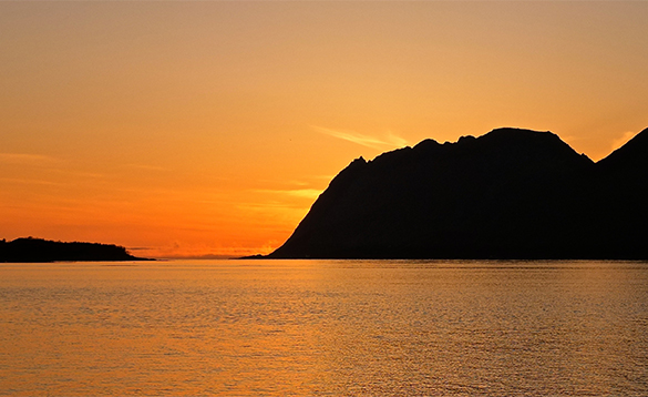 Sunsetting behind a mountain on a fjord in Norway/