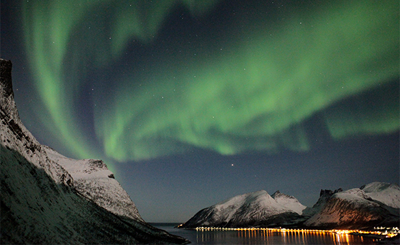 Northern lights over snow capped mountains/