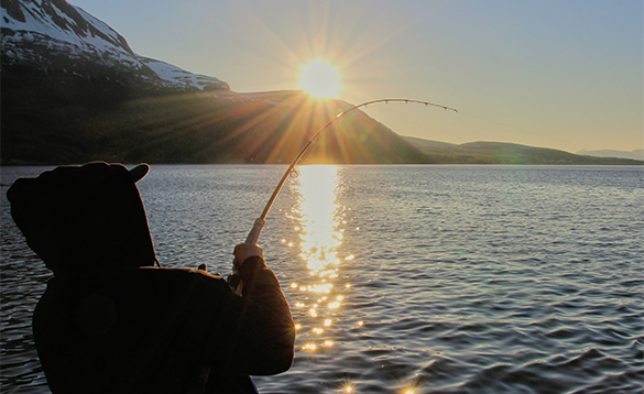 Angler fishing on a fjord in Norway as the sun rises over some hills/