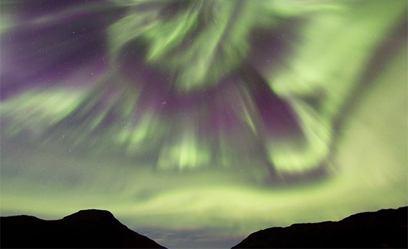 Green northern lights in the sky over some dark hills in Norway/