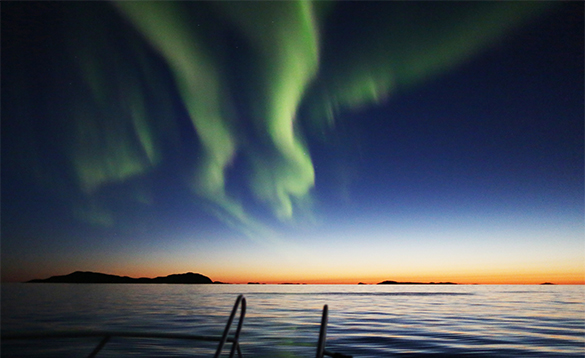 Green northern lights over a fjord in North Norway/