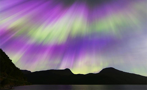 Green and purple northern lights over hills in north Norway/