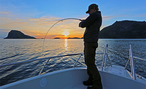 Angler standing on a boat fishing as the sun sets over a fjord in Norway/