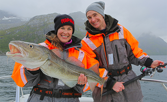 Lady angler holding a cod standing with a man holding a fishing rod in north Norway/