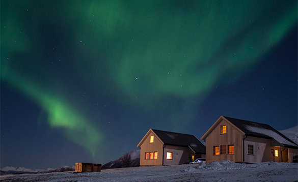 Northern Lights above two cabins at Lyngen North camp/