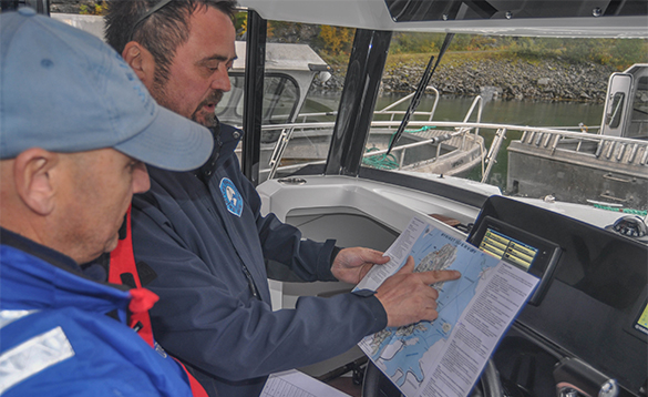 Two anglers in a boat studying sea charts/