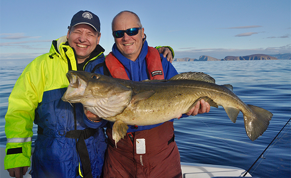 Two anglers on a boat in north Norway, one holding a cod/