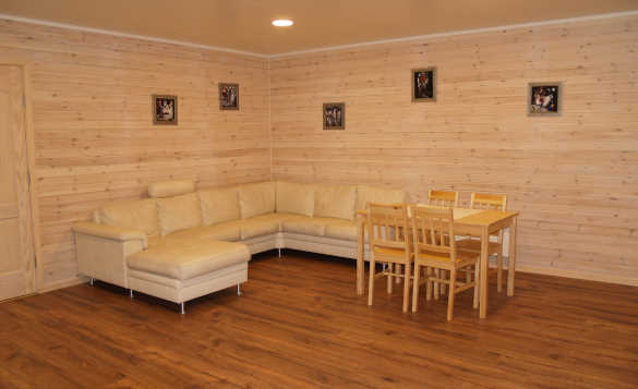Lounge in a self-catering property at Vikran Fishing Centre with corner white leather settee and pine table and chairs/