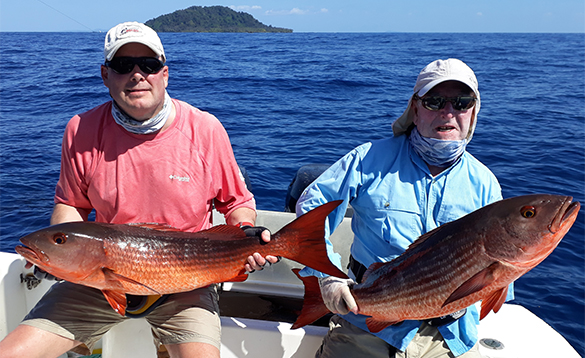 Two anglers sat on a boat with two cubera fish/
