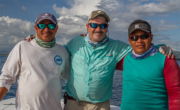 Three anglers standing on a boat on a fishing trip to Panama/