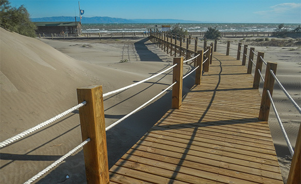 Wooden walkway leading across sand dunes towards the sea/