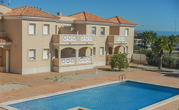 Spanish villa apartments with balconies beside a swimming pool/