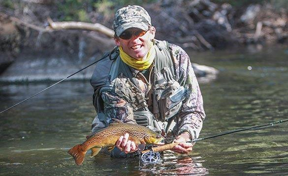 angler waist high in a river holding a brown trout that he has just caught/