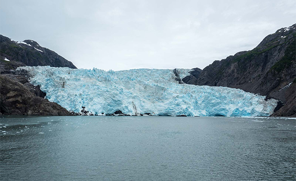 Glacier between hills leading to a lake shore/