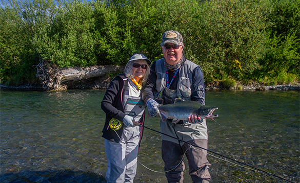 Two anglers with a coho salmon caught in Alaska/