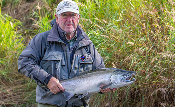 Angler holding a coho salmon caught in Alaska/