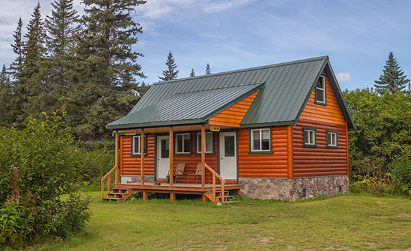 log cabin painted dark orange with porch surrounded by fir trees/