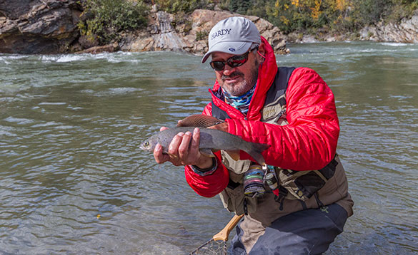 angler holding a grayling standing by a river/