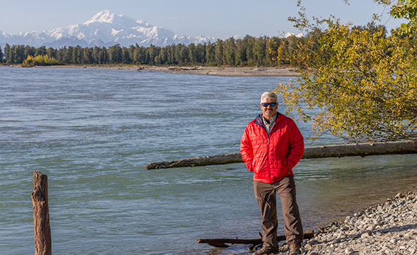 man in red coat standing beside a large lake with forests and snow capped mountains in the background/