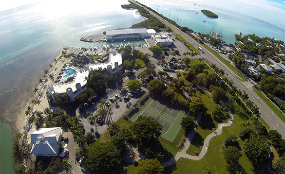 aerial view of a holiday resort in the Florida Keys with marina, two tennis courts and swimming pool set amongst trees/