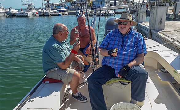 Group of anglers sitting on a boat enjoying ice creams/