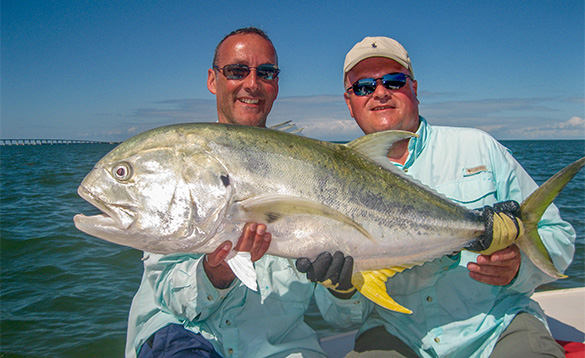 Two anglers sitting on a boat holding a jack fish caught in Florida/