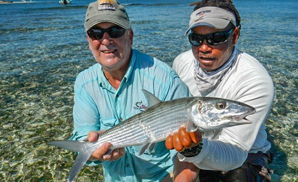 Two anglers holding a bonefish caught in Belize/
