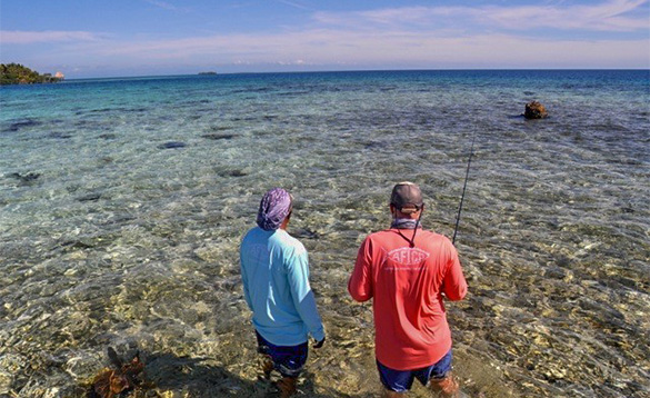 Two anglers stood in shallow water fishing in Belize/