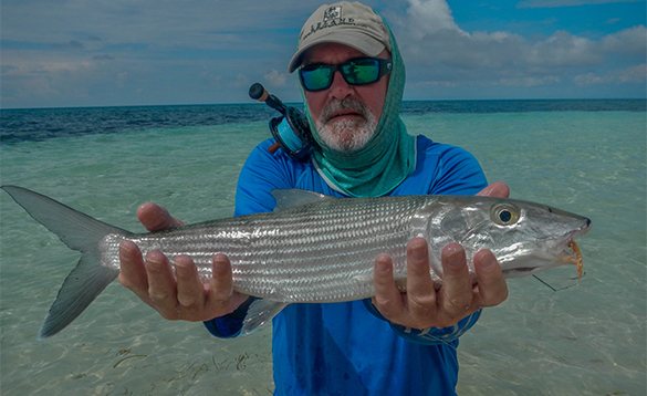 Angler holding a bonefish caught in Belize/