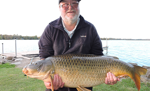 Angler holding a carp caught at Lakeside Cottages/