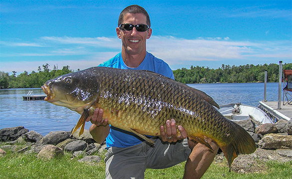 Angler holding a large carp caught in Canada/