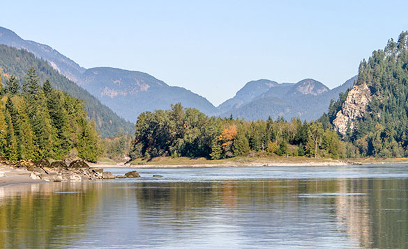 The Fraser River in British Columbia flowing past tree covered hills and mountains/