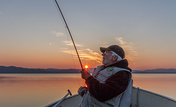 Angler fishing from a boat in a river at sunset/