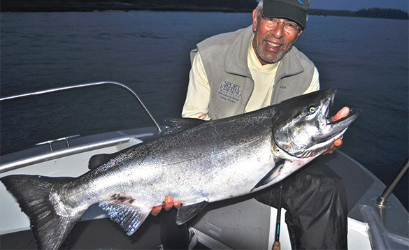 Angler sat on a boat holding a Chinook salmon/