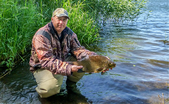 angler stood in the shallows of a river holding a bream/