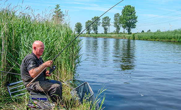 angler fishing from the grassy bank of a canal in Holland/