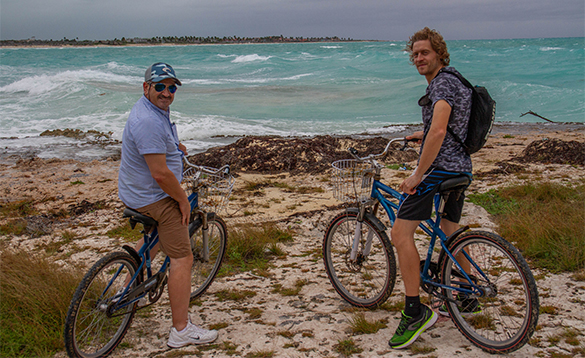 Two men on mountain bikes beside the sea in Cuba/