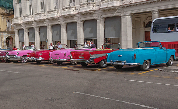 Old cars parked outside a building in Havana, Cuba/