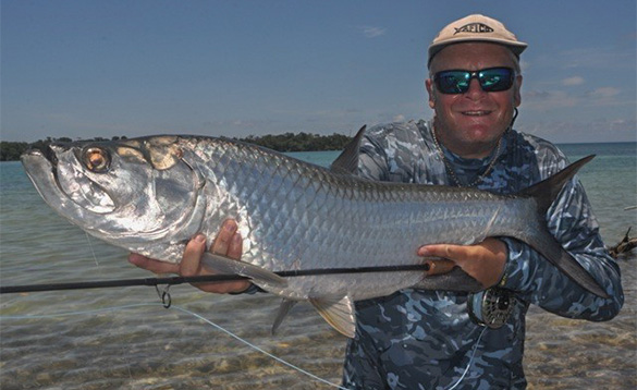 Angler holding a tarpon caught in Belize/