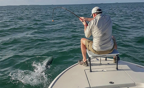 Angler sat on a boat fishing in Florida for tarpon/