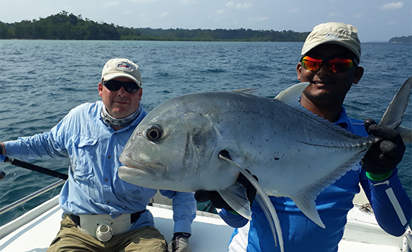 Two anglers in a boat in the Andaman Islands, one holding a recently caught GT fish/