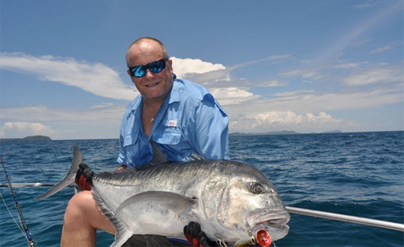Angler sat on a boat in the Andaman Islands holding a recently caught GT fish/