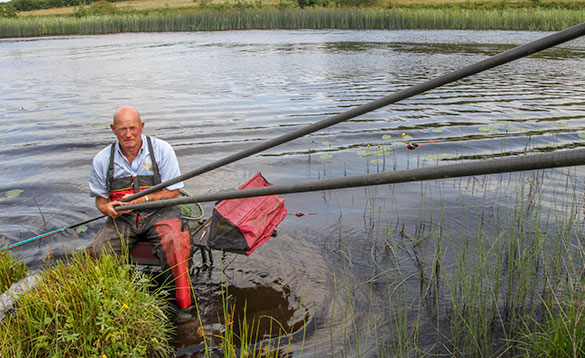 angler sitting on a tackle box in water at the edge of a reedy shore/