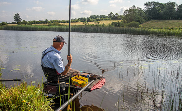angler catching a fish whilst sitting on a tackle box at the edge of a river/