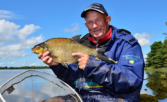 Angler sat beside Lough Derg holding a recently caught bream /