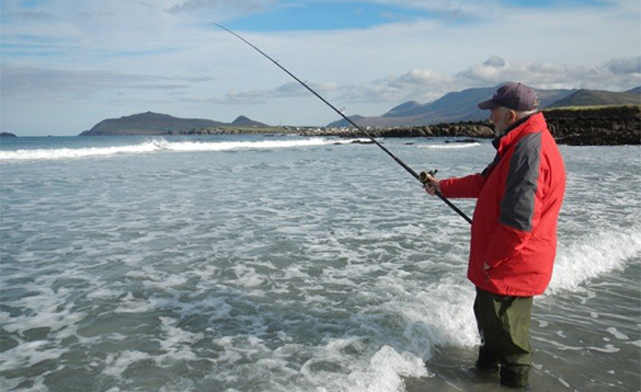 angler sea fishing whilst standing on the shoreline with mountains in the background/