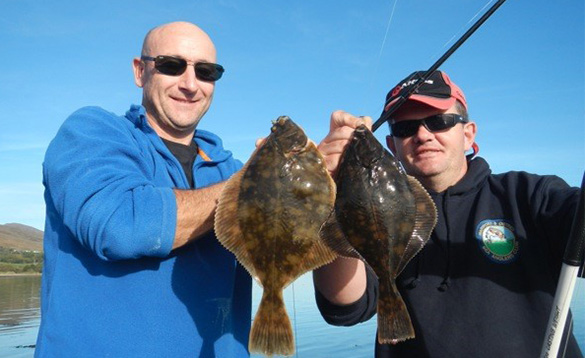 two sea anglers each holding a brown spotted flat fish/